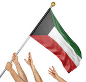 Team of peoples hands raising the Kuwait national flag Royalty Free Stock Photography