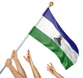 Team of peoples hands raising the Lesotho national flag. 3D rendering isolated on white background Stock Photo