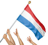 Team of peoples hands raising the Luxembourg national flag. 3D rendering isolated on white background Stock Image