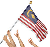 Team of peoples hands raising the Malaysia national flag stock photos