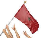 Team of peoples hands raising the Morocco national flag. 3D rendering isolated on white background Royalty Free Stock Image