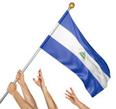 Team of peoples hands raising the Nicaragua national flag. 3D rendering isolated on white background stock photo