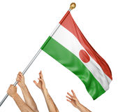 Team of peoples hands raising the Niger national flag. 3D rendering isolated on white background Stock Image