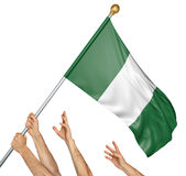 Team of peoples hands raising the Nigeria national flag. 3D rendering isolated on white background Royalty Free Stock Photo