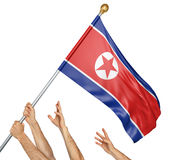 Team of peoples hands raising the North Korea national flag. 3D rendering isolated on white background Royalty Free Stock Photography