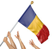 Team of peoples hands raising the Romania national flag stock photography