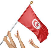 Team of peoples hands raising the Tunisia national flag. 3D rendering isolated on white background Royalty Free Stock Photo