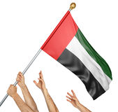 Team of peoples hands raising the United Arab Emirates national flag. 3D rendering isolated on white background Stock Image