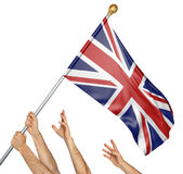 Team of peoples hands raising the United Kingdom national flag. 3D rendering isolated on white background Royalty Free Stock Photography