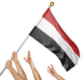 Team of peoples hands raising the Yemen national flag. 3D rendering isolated on white background Stock Photography
