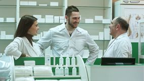 Team of pharmacist chemist woman and man standing in pharmacy drugstore and talking positive. Professional shot in 4K resolution. 081. You can use it e.g. in stock video