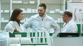 Team of pharmacist chemist woman and man standing in pharmacy drugstore and talking positive royalty free stock photo