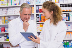 Team of pharmacist looking at tablet pc. At hospital pharmacy Royalty Free Stock Photos