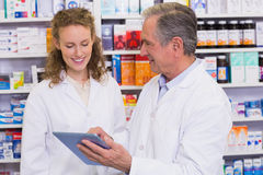 Team of pharmacist looking at tablet pc Stock Photo