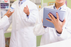 Team of pharmacist using tablet and holding medication Royalty Free Stock Photo
