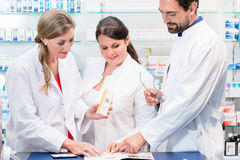 Team of pharmacists in drug store checking pharmaceuticals Royalty Free Stock Photo