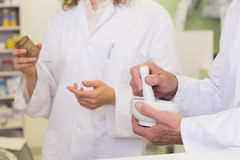 Team of pharmacists holding medicines and mortar Stock Photo