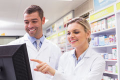 Team of pharmacists looking at computer stock photos