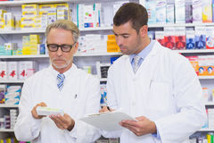 Team of pharmacists looking at medicine box Stock Images