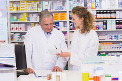Team of pharmacists looking at prescription Royalty Free Stock Photos