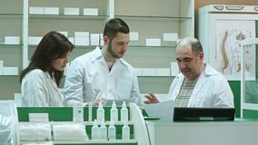 Team of pharmacists working at pharmacy drugstore, senior pharmacist is not satisfied with students job stock video