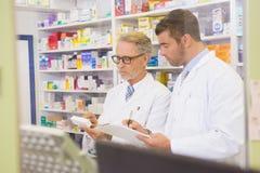 Team of pharmacists writing on clipboard Stock Photos