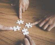 Team placing four puzzles jigsaw for team concept Royalty Free Stock Photo