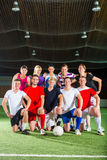 Team playing football or soccer sport indoor. Men and women in mixed sport team playing football or soccer indoor Stock Photo