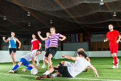Team playing football or soccer sport indoor. Men and women in mixed sport team playing football or soccer indoor and trying to score goal Stock Photo