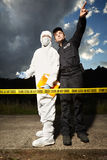 Team of police man and technician behind barrier tape Royalty Free Stock Images