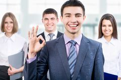 Team. Portrait of business men showing ok sign with cheerful team in background Stock Image