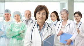 Team portrait of medical professionals. Team of medical professionals lead by senior female doctor looking at camera, smiling Royalty Free Stock Image