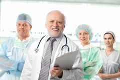 Team portrait of medical professionals. Team of medical professionals lead by senior white haired doctor looking at camera, smiling Royalty Free Stock Images