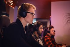 A team of professional cyber sportmans, trains for the championship, plays in a multiplayer video game on pc in a gaming. Club stock photography
