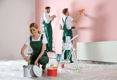 Team of professional decorators painting wall. Home repair service. Team of professional decorators painting wall indoors. Home repair service stock photo