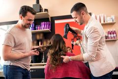 Professional hairdresser take care of clients hair at beauty sal. Team professional hairdresser take care of clients hair at beauty salon royalty free stock image