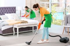 Team of professional janitors in uniform cleaning bedroom stock images