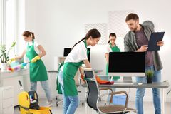 Team of professional janitors in uniform office royalty free stock images