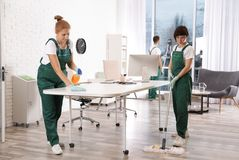 Team of professional janitors working in modern office royalty free stock photos