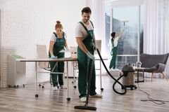 Team of professional janitors working in office. Cleaning service