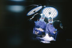 Team of professional surgeons performing surgery. In hospital. Group of surgeons performing surgical procedure on patient in operation room royalty free stock photography
