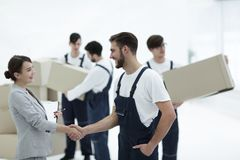 Manager with clipboard shaking hands with movers. stock images
