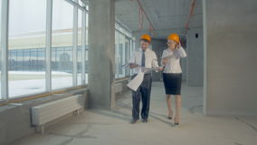 Team of professionals - engineer and architect - inspecting unfinished industrial building, construction site. 4K stock footage