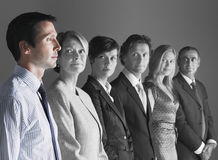 Team of professionals looking at colleague against gray background Royalty Free Stock Photography