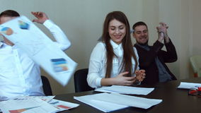 Team of professionals, sitting around a conference table throw their papers stock footage