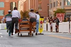 Team Pushes Bed Down Street In Mattress Race Stock Photo