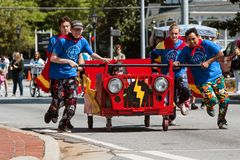 Team Pushes Bed On Wheels In Charity Fundraiser Event Royalty Free Stock Image