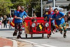 Team Pushes Bed On Wheels im Nächstenliebe-Geldbeschaffer-Ereignis lizenzfreies stockbild