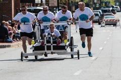Team Pushes uma cama roda sobre dentro o evento do Fundraiser da caridade foto de stock royalty free