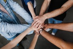 Team put hands together, show connection and alliance, Teambuilding in office, young businessmen and women in casual